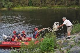 Elmsford firefighters tying up to the shore.