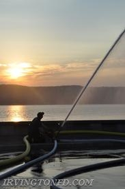Lt. Danny Billings checking out the sunset as well as utilizing the hose line.  Photo credit: Lt. Dowd