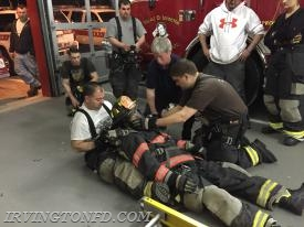 Lt. Mangiacotti removing a 'downed' members air pack and gear along with FF L. Lambros.