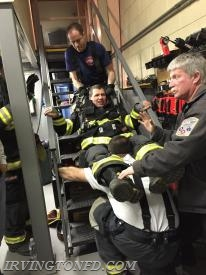 FF J. Kimmel pulls Ex-Chief Jim Ruffler up the stairs with FF L. Lambros at the feet.