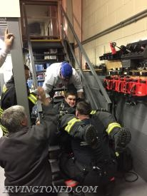FF P. Wool pulling Lt. Mangiacotti up the stairs along with FF P. Colantuono assisting at the feet.
