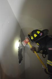 Firefighters breaching a wall.