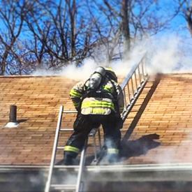 Chief Trama laddering above the fire for ventilation operations. Photo courtesy of Jared Rosenberg.