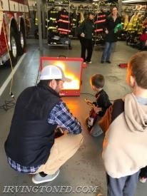 Parents and children learning how to use a fire extinguisher with our demo.