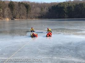 A firefighter is pulled from the ice hole during a training exercise.